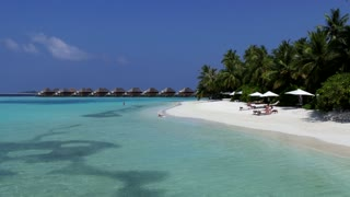 White sand beach in Vakarufalhi atoll, Maldives, Asia, Indian Ocean. People swimming and relaxing during holidays in exclusive resort. Blue sea waters, coral reef and palm trees. Travel and tourism