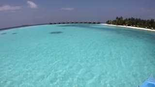 White sand beach in Vakarufalhi atoll, Maldives, Asia, Indian Ocean. People swimming and relaxing during vacation in luxury resort. Crystal clear sea water, coral reef and palms. Fisheye view