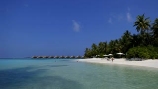 White sand beach in Vakarufalhi atoll, Maldives, Asia, Indian Ocean. People swimming and relaxing during vacation in luxury resort. Crystal clear sea water, coral reef and palms. Time-lapse