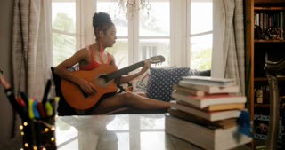 Woman Playing Classic Guitar And Singing In Her Room