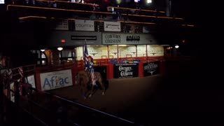 Young American cowgirl riding horse at rodeo and holding US flag in Cowtown Coliseum, arena in the stockyards of Forth Worth, Texas, United States of America