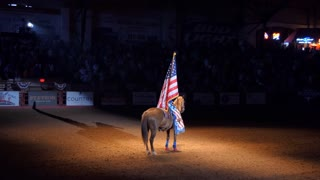 Young American woman riding horse at rodeo and holding US flag for the national anthem in Cowtown Coliseum, arena in the stockyards of Forth Worth, Texas, United States of America