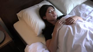 Young Asian woman sleeping in bed at home. Restless sleep for girl in bedroom. People suffering with anxiety disorder and having health problems