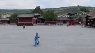 Young Chinese people training, child working out, boy exercising with sword for traditional martial arts in Tianshui city square, China, Asia