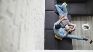 Young Couple Hugging and Laughing on Sofa