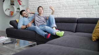Young Couple Taking Selfie On Sofa At Home
