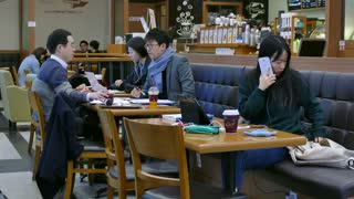 Young Korean student studying with mobile phone and iPad tablet, Asian people working in a cafeteria, busy businessmen with papers, young woman having breakfast in city bar. Seoul, South Korea, Asia
