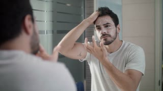 Young Man Applying Anti-aging Cream On Face For Skin Care