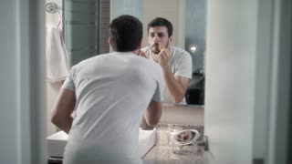Young Man Trimming Nasal Hair For Male Beauty In Bathroom