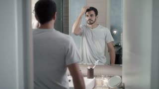 Young Man Worried For Hair Loss And Looking At Mirror
