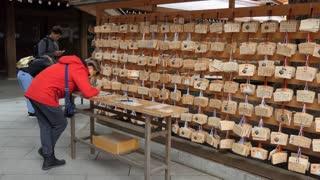 Young man writing wish on votive tablet, wishing plaque, wooden prayer tablet at Meiji Jingu or Meiji Jingo Shrine in Tokyo, Japan, Asia