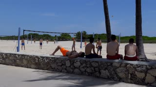 Young people playing beach volleyball in South Beach, Miami Beach, Florida, USA. Friends on summer vacation near the sea in America