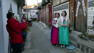 Young women wearing hanbok, traditional Korean dress. Asian girls, friends posing for a souvenir picture in Bukchon Hanok Village, a Korean traditional village in Seoul, South Korea, Asia