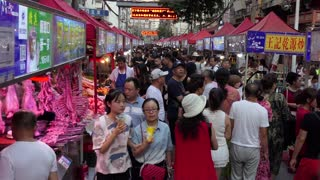 Zhengning Road, night market, food street in Lanzhou, Gansu province, China, Asia. Fair with stalls and shops selling Asian food. People buying snacks and dinner
