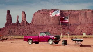 View of Monument Valley Navajo Tribal Park, Arizona, United States of America, USA with pick-up truck and shop selling native american silver jewels and souvenirs. Copy space, sequence