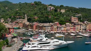 View of Portofino in Liguria, Italy. Beautiful and famous Mediterranean sea town in the Italian Riviera. Travel, tourist destination, landscape, luxury yachts in harbor, boats in port