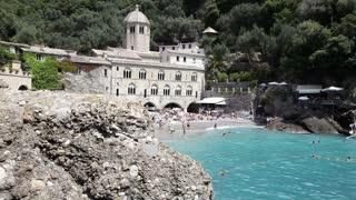 View of San Fruttuoso di Camogli, Italy, Italian Riviera, with sea, rocky beach and people swimming