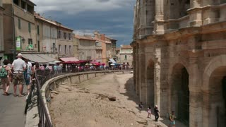 View of the famous town of Arles in Provence, Southern France. Beautiful French town with tourist attractions and monuments. Tourists walking and people visiting the Roman amphitheatre
