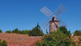 View of windmill near the traditional medieval village of La Couvertoirade, southern France. Beautiful typical French town, monument and tourist attraction. Travel, holiday in Europe
