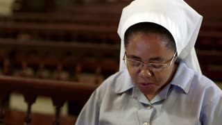 Woman and christian faith, catholic sister, nun praying with holy rosary in catholic church during mass