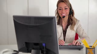 Woman at work as secretary, customer care operator at helpdesk, talking on telephone with headset in office