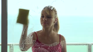 Woman Doing Chores Latherin and Wiping Window Glass At Home