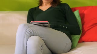 Woman relaxing on sofa with ebook 2of3