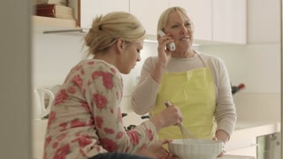 Women in kitchen at home, mother speaking on the phone while daughter helps her cooking