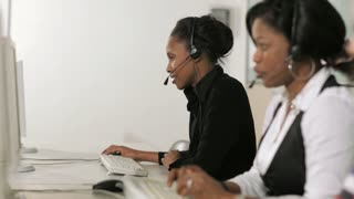 Women working as customer service representatives at reception desk, talking on telephone with headset