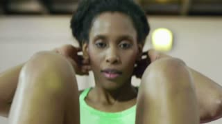 Young african american woman in sportswear exercising abdominal muscles on pad in fitness gym