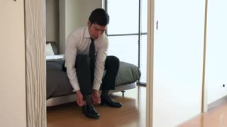 Young Asian business man in bedroom at home. Early morning routine with Japanese businessman getting ready for office work with manager dress and elegant shoes, tying shoelaces