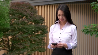 Young Asian Woman Texting Message With Smartphone Near Office Smiling