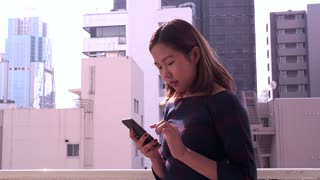 Young Chinese Asian Businesswoman Talking On Phone Near Office Buildings