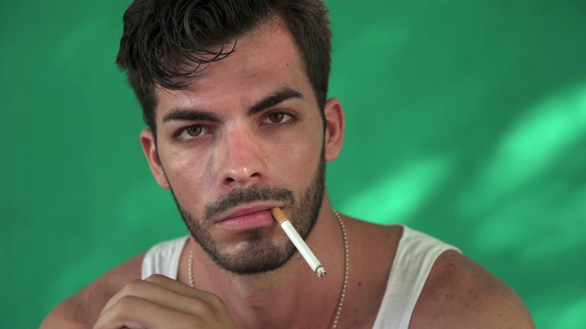 Young Hispanic Man Smoking Cigarette And Blowing Smoke