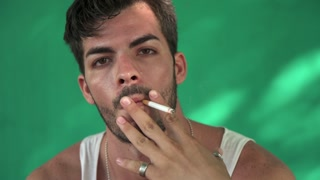 Young Hispanic Man Smoking Cigarette And Blowing Smoke