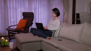 Young Japanese woman talking on cell phone, Asian girl speaking with  smartphone, mobile telephone on sofa in living room at home. Busy people using laptop pc, notebook computer for work