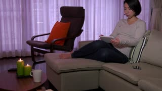 Young Japanese woman touching ipad monitor, Asian girl using digital tablet, computer on sofa in living room at home. Wireless technology for internet and wi-fi email, lifestyle, relax