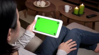 Young Japanese woman touching ipad monitor, Asian girl using digital tablet with green screen, computer at home. Wireless technology for internet and wi-fi email, lifestyle, relax