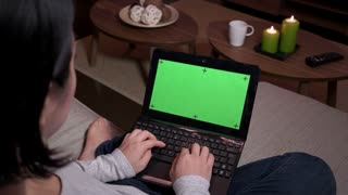 Young Japanese woman typing on keyboard, Asian girl using laptop pc with green screen, notebook computer monitor at home. Wireless technology for internet and wi-fi email, lifestyle