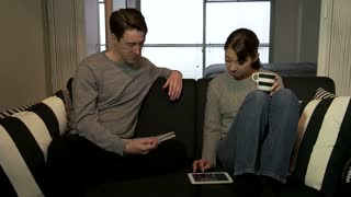 Young Man And Woman Husband Wife Using Ipad Tablet Smiling