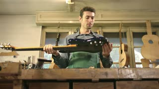 Young man at work as craftsman in workshop with guitars and musical instruments. Rack focus