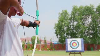 Young man training at archery with bow and arrows, people, sports, fun and leisure, recreation
