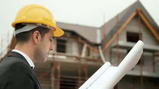 Young man working as engineer in new apartment buildings, looking at building plan in construction site. Sequence