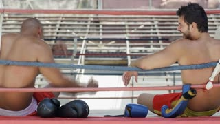 Young men friends people laughing relaxing in boxing ring gym