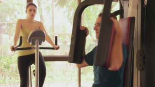 Young people and leisure, lifestyle and fun, leisure activity, man and woman on holiday. Sport athletes training, working out in fitness club with gym equipment and bike