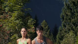 Young people and sports, boy and girl jogging on mountain track. Slow motion