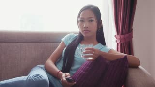 Young people at home, lifestyle and relax, portrait of happy beautiful Asian woman lying on sofa, watching television, tv channel hopping with remote control, and drinking water