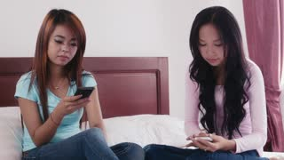 Young people, cell phone, social network and technology, portrait of two happy Asian girls smiling, using smartphones in bedroom at home, looking at camera