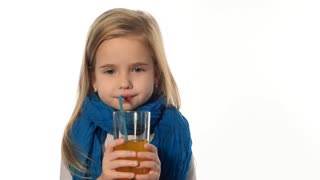 Blond little girl drinking juice