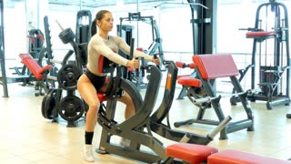 Athlete woman trains muscles of the back in the gym